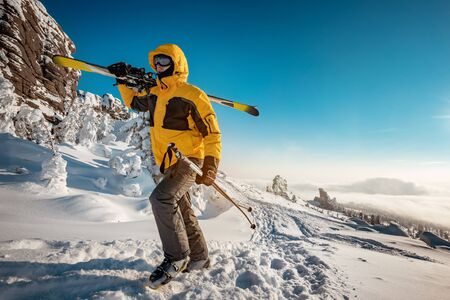 Skier with ski in hands goes uphill for backcountry skiing. Ski resort concept