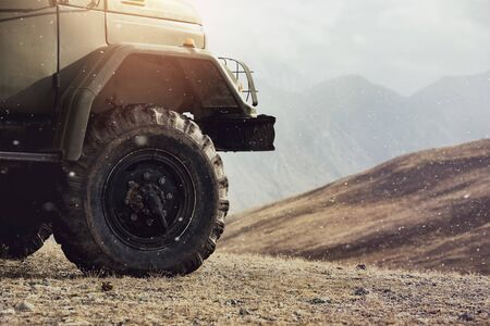 Close up photo of 4x4 offroad car wheel in mountains