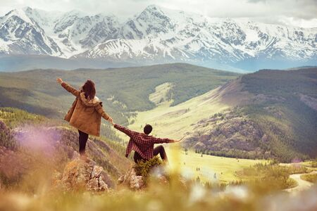 Happy couple with raised arms is having fun on view point in mountains Imagens - 131676959