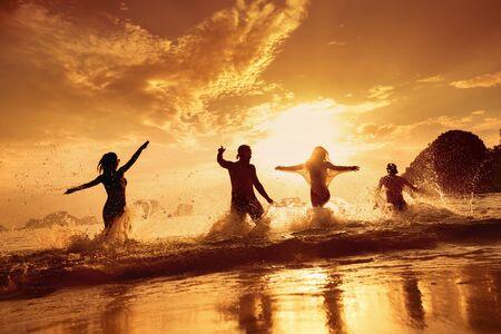 Four happy friends runs and having fun at beautiful sunset sea beach Imagens