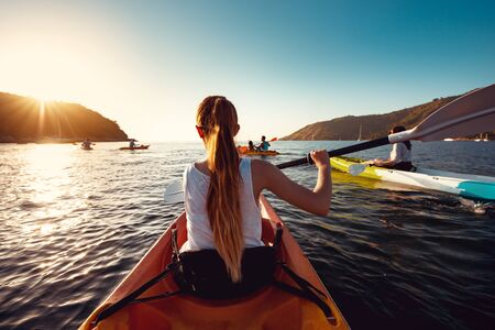 Big group of kayaks with friends is walking in sunset sea bay Imagens - 131782518