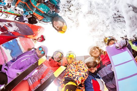 Big group of happy friends skiers and snowboarders stands in circle and looks down. Ski resort
