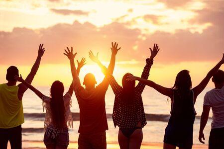 Sylwetki sześciu szczęśliwych przyjaciół z uniesionymi rękoma stoją na tle pięknej plaży o zachodzie słońca