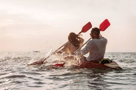 Happy couple walks by sea kayak at sunset