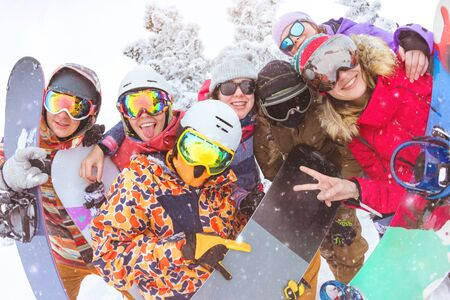Big group of friends is having fun at ski resort. Happy skiers and snowboarders are taking photo together
