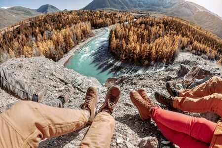 Four friends sits and looks on river and mountains. Close up photo of legs
