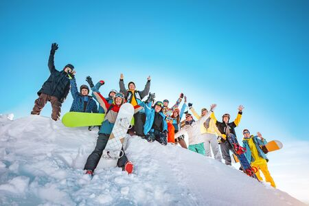 Big group of happy skiers and snowboarders with raised arms stands on snowdrift at ski resort. Ski and snowboard concept
