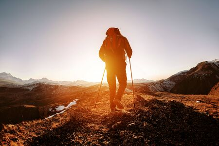 Silhouette of hiker with backpack and walking poles is going in mountains and sunset Stok Fotoğraf