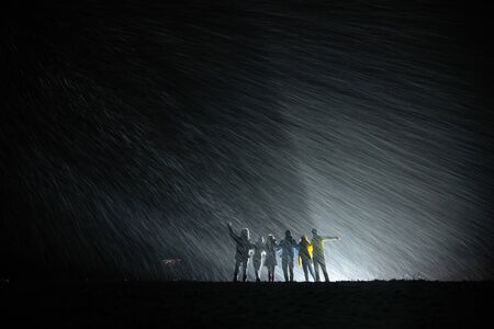 Group of silhouettes stands together against snowfall and back light and having fun