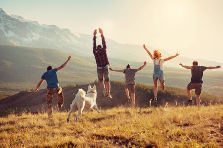 Group of happy friends are having fun, runs and jumps in mountains at sunset