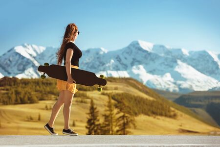 Young girl stands with longboard on straight road against mountains