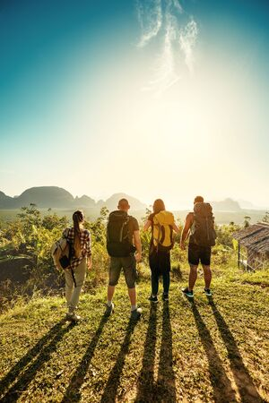 Four friends hikers and travellers stands on sunrise viewpoint on sea and islands Stok Fotoğraf