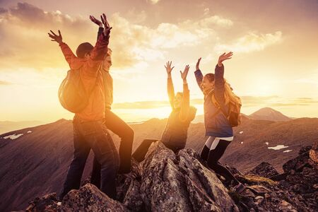 Four happy hikers celebrating climbing on mountain top at sunset