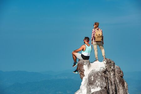 Two hikers are relaxing on mountain top on big rock Stok Fotoğraf