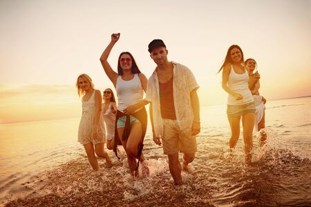 Group of young friends are having fun at sunset beach party Stok Fotoğraf