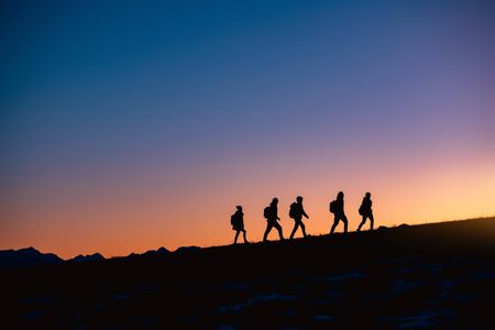 Silhouettes of group of hikers going uphill at sunset mountain Stok Fotoğraf