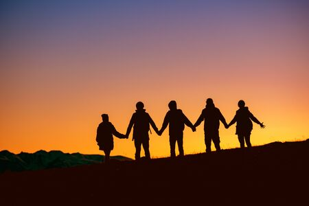 Silhouettes of group of friends are standing together at sunset time against mountains Stok Fotoğraf