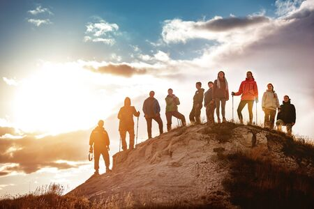Big group of hikers stands against sunset. Hiking or trekking concept