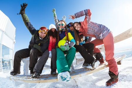 Five happy friends skiers and snowboarders are having fun and posing together at ski resort Stok Fotoğraf