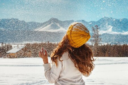 Beautiful girl is playing with snow against mountains