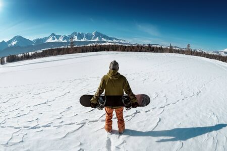 Snowboarder stands with snowboard against mountains. Backcountry concept Stok Fotoğraf