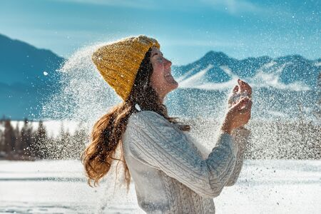 Happy beautiful girl plays with snow powder against forest and mountains