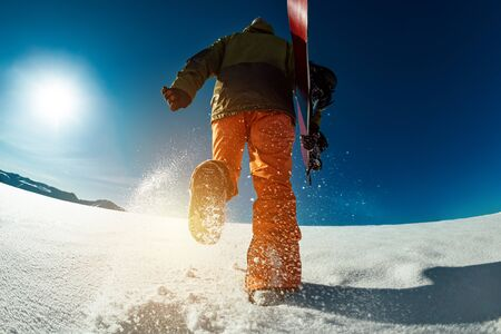 Snowboarder goes uphill with snowboard in hands. Backcountry skiing concept Stok Fotoğraf