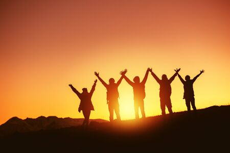 Group of happy peoples silhouettes stands with raised arms against sunset and mountains