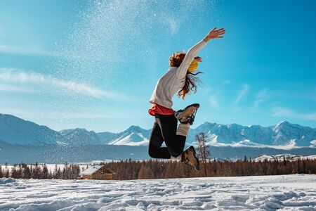 Happy girl jumps with snow against snowcapped mountains. Winter concept Stok Fotoğraf