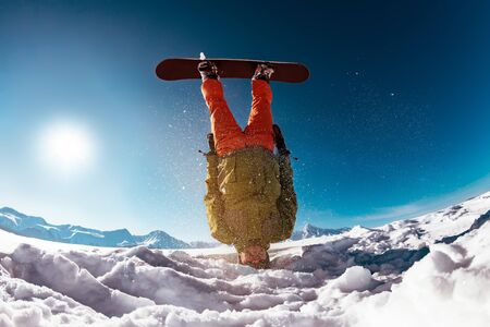 Snowboarder stands upside down on head against mountains.