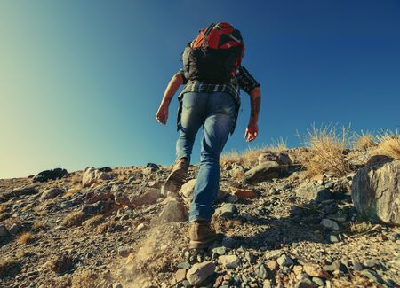 Hiker or backpacker goes uphill with big backpack. Trekking tourism concept