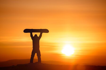 Snowboarder holds snowboard above the head on background of sunset sun and sky.