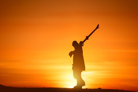Skier with ski in hands walks at sunset. Imagens