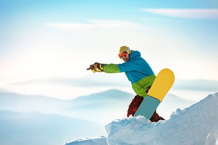 Snowboarder stands with snowboard on ski slope and point at something. Imagens