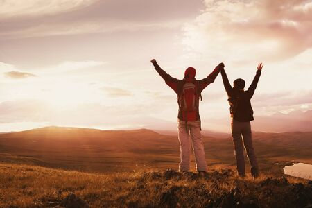 Two happy hikers stands with raised arms against mountains and sunset
