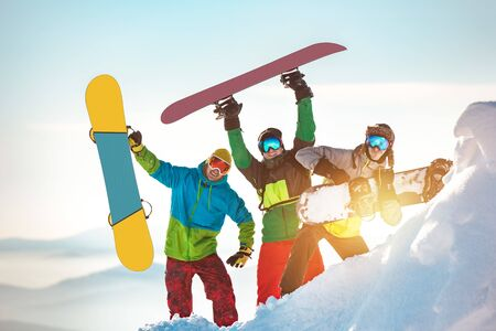 Three happy snowboarders are having fun and posing with snowboards