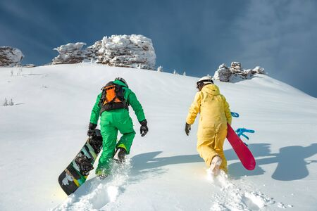 Two snowboarders walking uphill. Backcountry skiing and snowboarding concept at ski resort