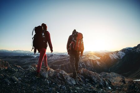 Two hikers male and female walks in sunset mountains Imagens