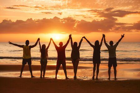 Eine Gruppe glücklicher Freunde amüsiert sich mit erhobenen Armen zusammen am Meeresstrand und genießt den Sonnenuntergang