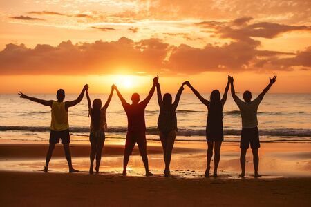 Group of happy friends are having fun with raised arms together at sea beach and enjoy sunset Imagens