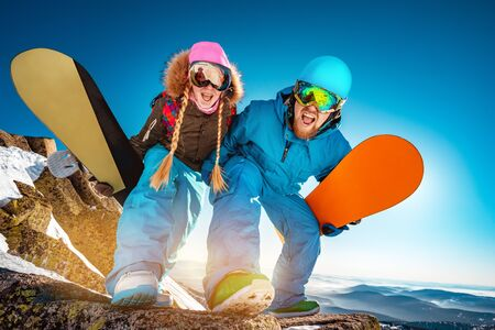 Couple of snowboarders male and female are having fun and posing for photo with snowboards