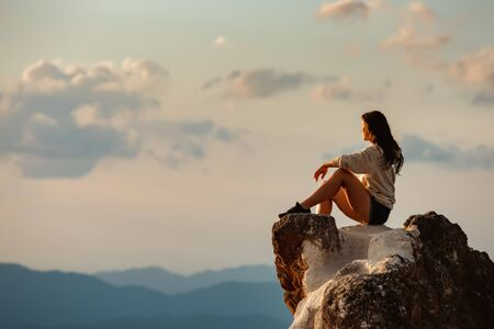 One sporty girl sits on big rock and looks at sunset sky and mountains