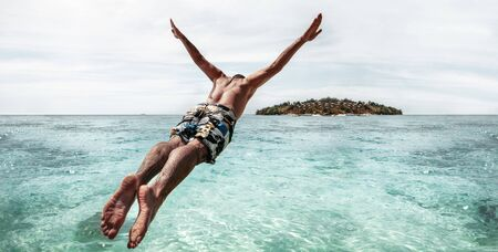 Sporty man jumps like athlete with raised arms in turquoise water