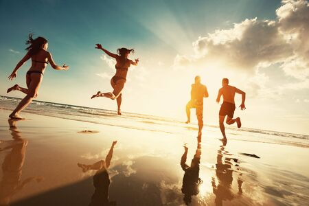 Four happy tourists runs to sunset sea beach. Beach vacations concept Imagens