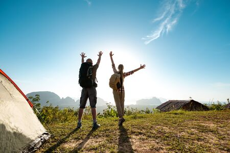 Two happy hikers male and female stands with raised arms at sunrise near tent