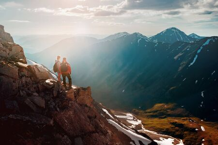 Two hikers male and female stands on a cliff in big mountains and enjoys sunset