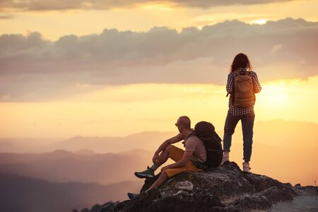 Couple hikers with backpacks are having rest on mountain top at sunset time