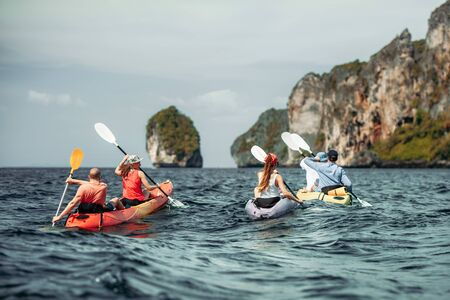 Group of young friends walks by sea kayaks under the islands. Krabi province, Phi-Phi islands, Thailand