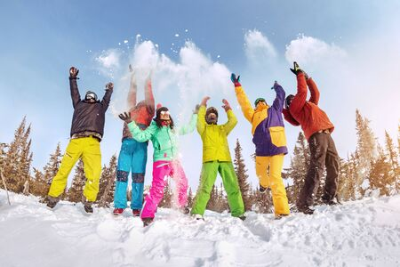 Group of happy friends skiers and snowboarders are having fun and tossing snow. Ski resort concept