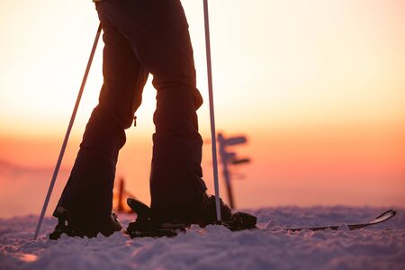 Close Up photo of female skiers legs with ski poles against sunset sky